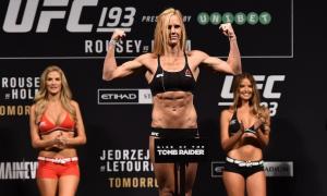Women UFC fighter standing on podium flexing